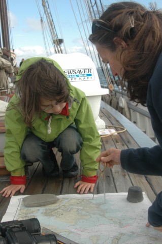 Captain Amanda teaches Alice how to measure distance with the dividers