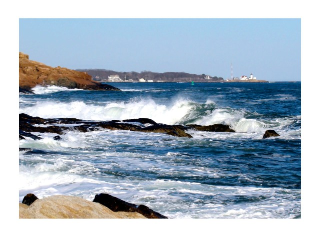 waves crashing on rocks of Magnolia with Eastern Point Light in the distance