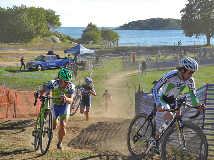 """This """"Cross"""" is dusty and  great event.  Our harbor is in the background. Part of the course is to dismount and run your bikes up four or five steps, and then mount up and speed on. What fun!"""