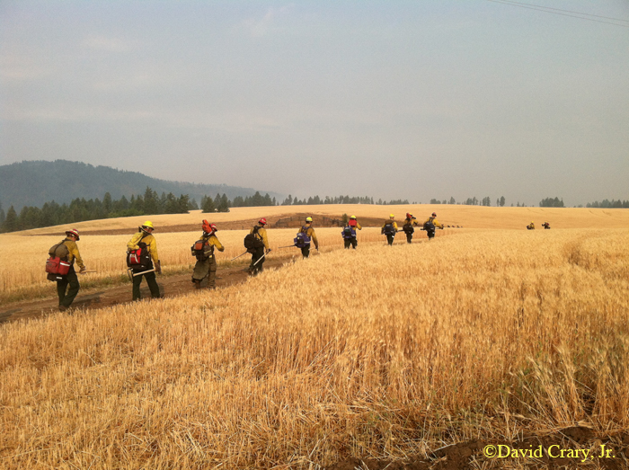 David Crary took this photo of his fire crew marching with their fire fighting tools and survival gear to do battle at the Incendiary Creek Fire in Idaho. If not careful, some of these brave professionals firefighters could suffer serious injury or worse.