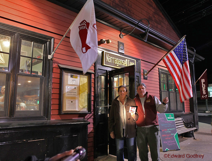 "I had a visit recently from two folks of Jamestown, RI. I have some familiarity with Jamestown, and we talked a bit. I sent them off with a sticka' and an assignment to represent in front of their favorite pub flying the Red Sox banner. They came thru: ""Pat O'Leary & Ed Godfrey had a great time in Gloucester (Ed likes the historic photos) & enjoyed the Paul Brady concert at Shalin Liu center Rockport. Will return again but not in summer, do not like the circus. We find fall and winter to be the best, just like here on the island in Jamestown."" Jamestown is a small island in between the mainland and Newport. It hosts a bridge on each side. http://www.narragansettcafe.com/"