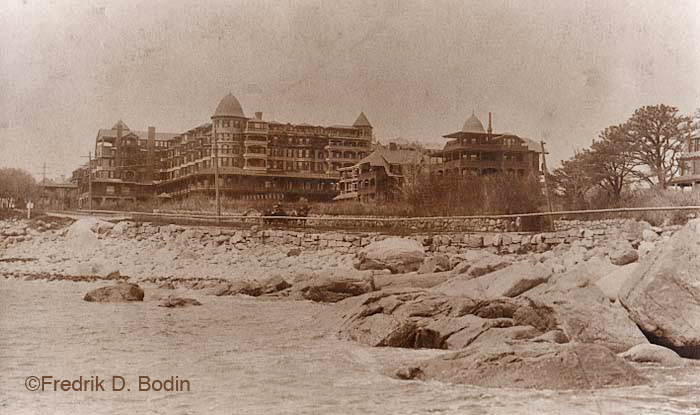 The Oceanside Hotel in Magnolia was built in 1878. With its 400 rooms, it was the 2nd largest hotel of its type in New England. Shore Road with a carriage underway is in the foreground. Sadly, the Oceanside burned to its foundation in 1958.