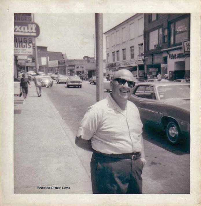 "From Brenda Grimes Davis: ""Fred...Here's a picture of Barney Marnoy who managed Benny Schred's fabric store...which was located where Passports (temporarily Village Pharmacy) is in the 1960s...he's standing just outside the door..I believe Benny was Barney's father-in-law."" Notice the Rexall sign on the left. That was the original location of Connors Pharmacy on Main Street."