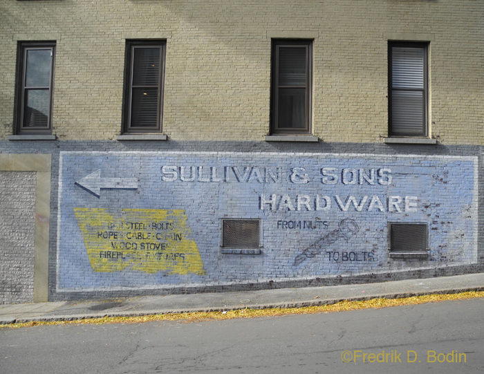 """A sign painted on the wall of Gabriel's Antiques, on Center Street. Made to look old and weathered. """"From Nuts to Bolts."""" HBO production."""