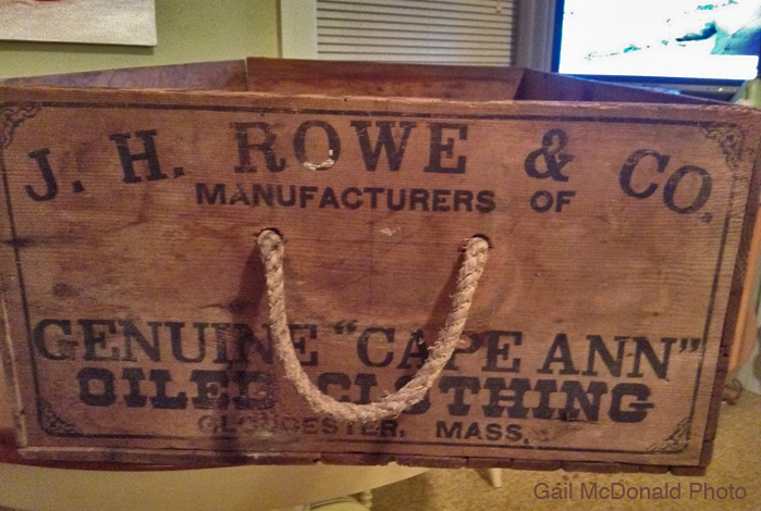 """My friend Gail McDonald would like to know more about this wooden box she acquired. It's a beautiful box. This is what I know: Joseph H. Rowe founded his oiled clothing company in 1884 in Gloucester. He improved apparel technology to be waterproof, especially useful for fishermen. His """"Mother Ann"""" brand manufactured coats, pants, Sou'westers (hats), boots, horse covers, and wagon covers. We have a Rowe's Wharf, where Cruiseport is now. Any additional information will be appreciated."""