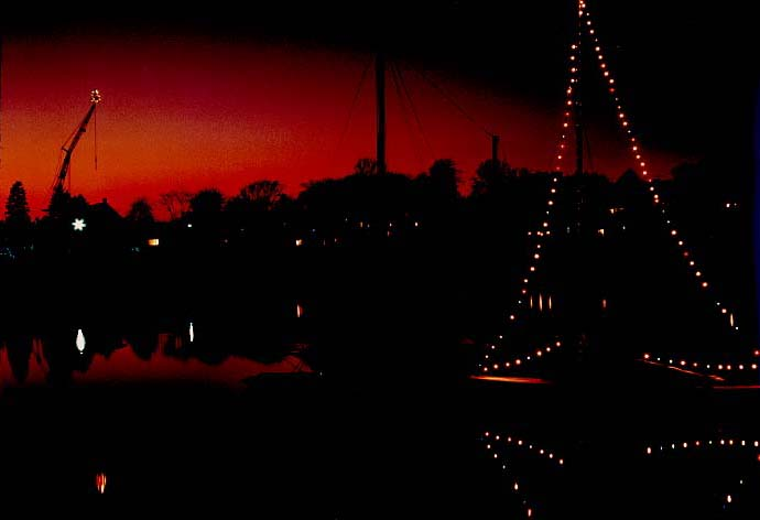"Christmas Eve! I took this photo at a Christmas party on East Main Street, looking across Smith Cove. The sailboat was decorated with lights, as was the crane at Bickford's boat yard on Rocky Neck. Co-owner Marco Taormina did that every year. He was a gruff but likable character. He loved to drink his ""green grenades,"" which were bottles of Heineken beer."
