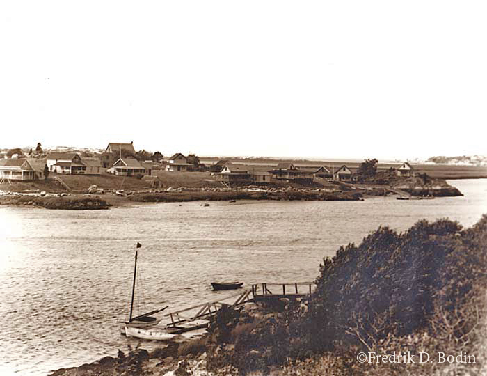 Three investors bought Merchants (or Pearce)  island about 1890: Edward Samuel Page, Mr. Kitchen, and another investor. They had trouble selling lots because of fresh water issues. This photo shows Merchants Island from Riverview, with the pier and float in the foreground, enabling the only access to the island. A handful of cottages still stand on Merchants, used in the summer only.