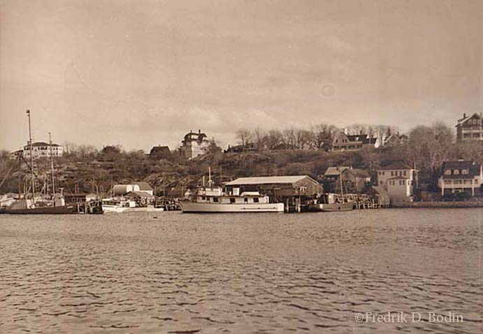"Smith Cove in East Gloucester was, and still is, populated by both fishing and pleasure boats. In the background of the photo is East Main Street, with Banner Hill rising above it. The boats, from left to right: Harpoon sword fishing boat ""Jaguar"" (previously named Lord Jim and also a WWII submarine chaser), owned by Dr. Fred Breed; ""Jumping Jennifer,"" Tom Morse's fishing boat; Party fishing boat ""Winner III,"" owned by Bobby Anderson; and the ""Naomi Bruce III,"" co-owned by Cy Tysver and the Shoares family. Vessel histories are complex, and all comments and corrections are welcome."