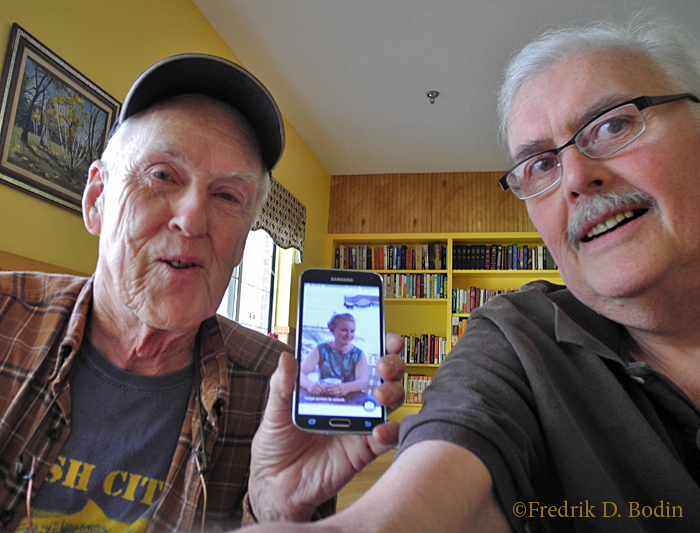 """My friend Al Bezanson visited me at Rehab, where I made my first """"selfie."""" Between us, on his cell phone, is Al's bride Phyllis in her 20's. Al was in Gloucester to work on his schooner Green Dragon for spring launching. It's always a pleasure to see Al and Phyllis in the gallery, and at their summer digs on Rocky Neck over a bottle of rum. I made a promise to myself to sail the Green Dragon this summer, and take another selfie of us at the wheel."""