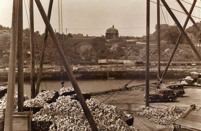 From the top of Granite Pier, we see a lot of going on at Gull Cove. Granite cobblestones, probably from nearby Flat Ledge Quarry, are ready to be loaded onto barges or schooners. Small gauge railroad cars sit on the other side of the cove, ready to haul granite from the quarry on the other side of the Keystone Bridge. Granite Street passes over the bridge, and past the Rockport Granite Company building, which is built with granite, of course!