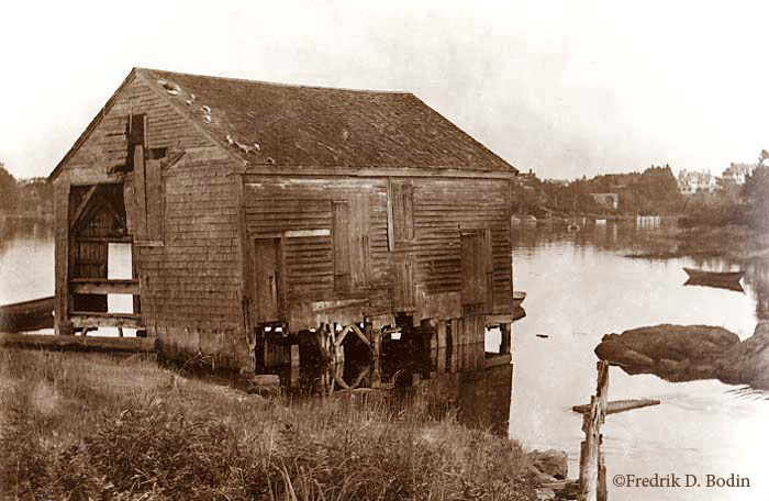 Israel Forster's Grist Mill  sat over Bennetts Brook on pilings. Manchester Harbor is behind it, with the town in the distance. Later, the mill was converted to produce furniture turnings (shaped parts of furniture, such as table legs).