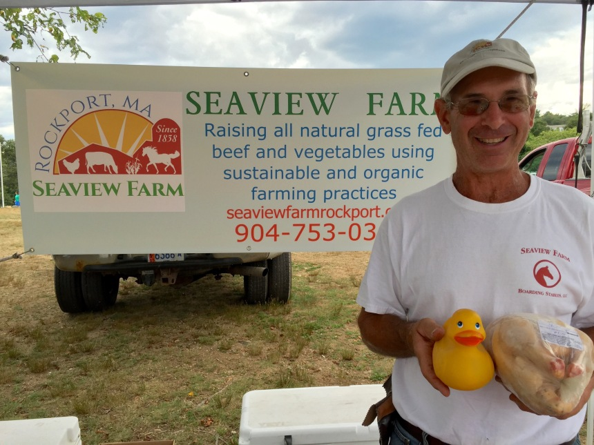 Ken from Seaview Farm at Cape Ann Farmers Market on Thursday. Meet him and the chicken that he is holding at the Rockport Farmers Market. (Chicken is in his left hand.)