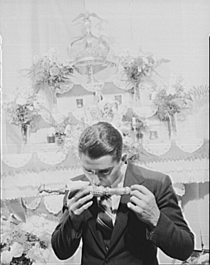 Frank Domingos kissing a vessel representing remains of a saint, during ceremonies at his father's home, part of the tri-annual fiesta of Pentacost. The celebration--including the chosing of an Imperator, and