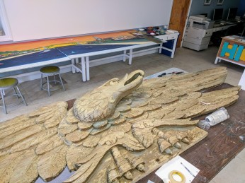 Works in progress: Jason Burrough helping mural. Carved eagle from Cameron's facade.