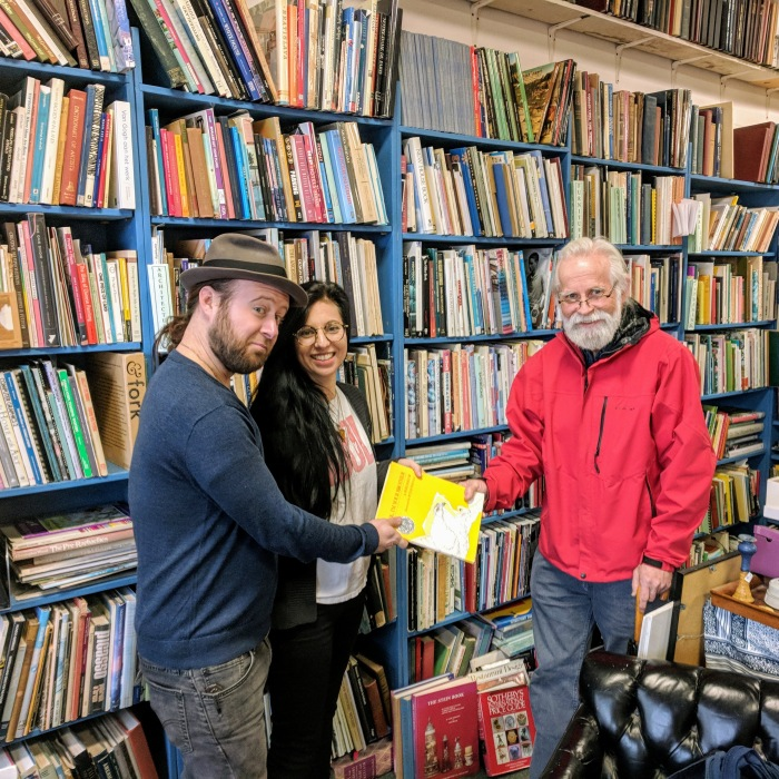 Passing the torch _portrait of BOB RITCHIE_used and rare books dealer_on his last day at Dogtown Books_with new owners_Lucas Cotterman_Caroline Harvey_Gloucester Ma_20181119_© c ryan.jpg